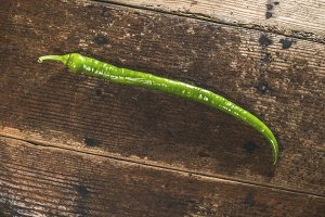 Green long pepper on wood