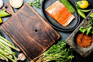 Raw salmon fillet and asparagus and herbs around wooden board. Food cooking background with copy space. Top view.