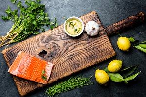 Raw salmon fillet, asparagus, lemons and herbs around wooden board. Food cooking background with copy space. Top view.