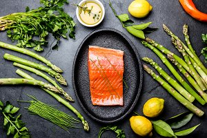 Raw salmon fillet. Asparagus, lemons, olive oil and herbs around plate with salmon. Food cooking background. Top view.