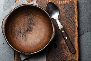 Cooking background. Vintage empty clay bowl on cutting boards, copy space