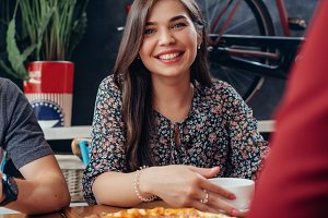 Portrait of young pretty smiling woman looking at camera sitting in restaurant drinking coffee and eating pizza with friends