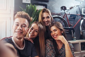 Young smiling teenagers taking selfie while having fun in stylish bar