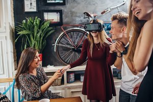 Excited young girl testing virtual reality headset while her friends watching, laughing and supporting her. Group of teenagers having fun time together indoors.