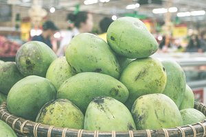Tropical fruits close up green mangoes in the asian shop. Bali island, Indonesia. Organic market.