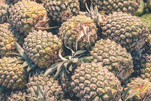 Pile of pineapples at asian organic market, closeup. Tropical island Bali, Indonesia.