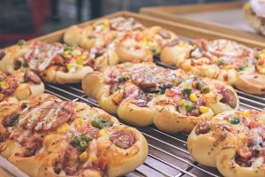 Mini pizzas with cheese, tomato, green beans, corn and sausages in the shoppin mall, small italian bakery. Tropical island of Bali, Indonesia.