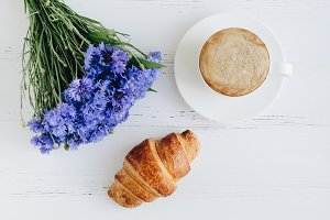 Cup of coffee with bouquet of blue cornflowers and croissant