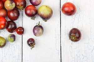 Different tomatoes on the white wooden background