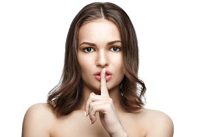 Portrait of beautiful woman with finger on lips, isolated