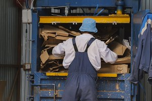 Worker on recycling of cardboard at industrial landfill, ecology concept