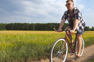 Sporty guy in sunglasses cycling along country trail outdoor. Young smiling man riding vintage bicycle at rural road over field. Male cyclist riding bike in the countryside. Healthy active lifestyle