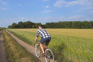 Young man riding vintage bicycle at the rural road over field. Sporty guy cycling along country trail outdoor. Male cyclist riding bike in the countryside. Healthy active lifestyle