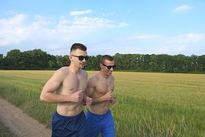 Two muscular men running and talking outdoors. Young smiling athletic guys jogging over the field. Male sportsmans training together at nature. Friends exercising outside. Healthy active lifestyle