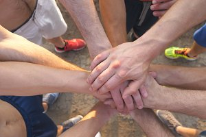 Many male hands getting together. Team of athletes putting arms together outdoor. Group of people joining hands together outside. Friends forming arms stack at nature. Teamwork Close up Top view