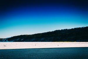 Horizontal vivid winter fishing on lake landscape background