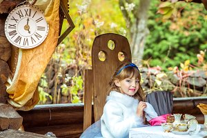 An little beautiful girl holding cylinder hat with ears like a rabbit in the hands at the table