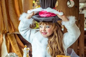 An little beautiful girl holding cylinder hat with ears like a rabbit over head at the table