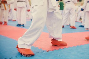 Karate training - group of karateka teenagers in red shoes and white kimono
