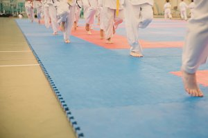 Group of karateka teenagers in kimono runs on tatami in the gym
