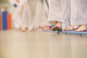 Karate training - teenagers in kimono runs on tatami in the gym