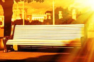 Horizontal bench in city park in light leak background