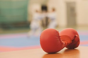 Red gloves for karate training on tatami during training, de-focused