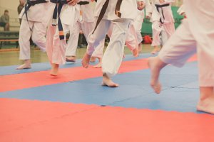 Group of karate sportsmen teenagers in kimono runs on tatami in the gym