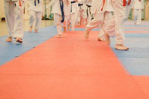 Karate training - young sportsmen in kimono runs on tatami in the gym