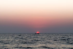 Solar disk boat people ocean sunset