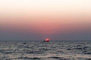Solar disk boat people ocean sunset