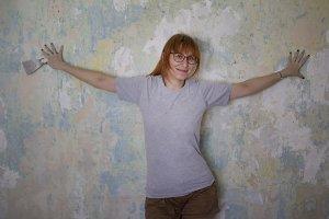 Home renovation - cute red hair woman with scraper near wall glues wallpaper