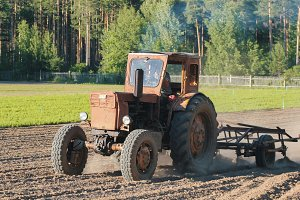 Preparing land with seedbed cultivator - tractor on field, agricultural works at farmlands