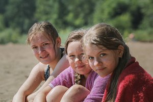 Happy three teen girlfriends on the beach after river swimming