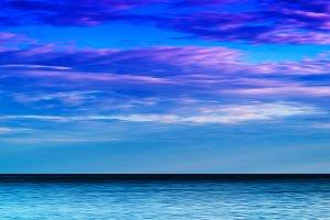 Horizontal vibrant ocean horizon with dramatic cloudscape backgr