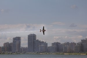 Small sport aircraft flying over modern city