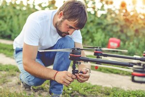 Young engineer preparing agriculture drone before flying