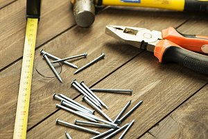 Stacked nails, hammer, pliers, and tape measure on brown wooden table. Construction tools. Horizontal sutdio shot.