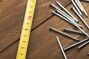 Stacked nails and tape measure on brown wooden table. Horizontal sutdio shot.  Construction tools
