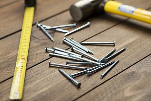 Stacked nails next to a hammer and tape measure on brown wooden table.  Construction tools