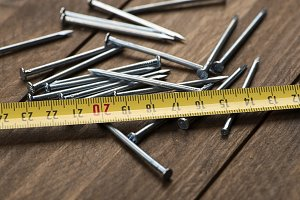 Stacked nails next to tape measure on brown wooden table.
