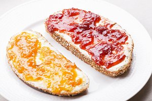 Two toasts with strawberry jam and peach on a tablecloth.