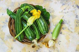 Fresh zucchini on wicker mat on Light background
