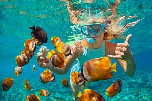 Girl snorkelling with fishes