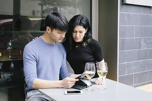 Multiethnic couple in a cafe looking at phone