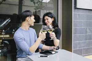 Couple of friends toasting with a glass of wine in a restaurant