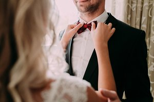 Bride fixes red bow tie on groom's neck while they stand near the window
