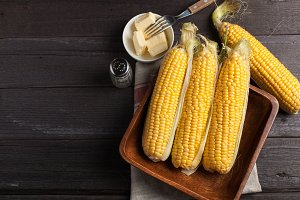 Fresh corn on the cob with salt and butter on wooden table, closeup, top view. Dark background with copy space