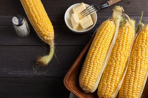 Fresh corn on the cob with salt and butter on wooden table, closeup, top view. Dark background