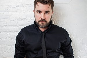 Portrait of a bearded serious man in a black shirt and tie against a white brick wall. The man is standing with his hands in his pockets